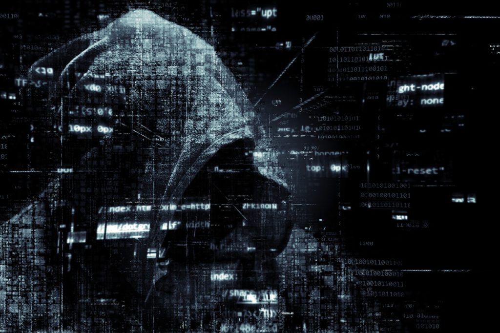 Image of a hooded figure on a black background with lines of computer code floating around them. Scam calls and why they're dangerous.